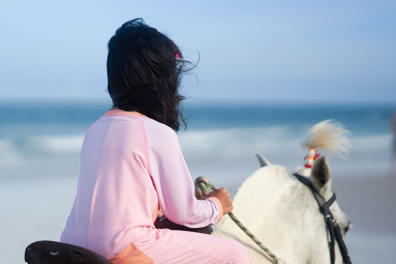 Rear view of girl sitting on horse on beach against sky