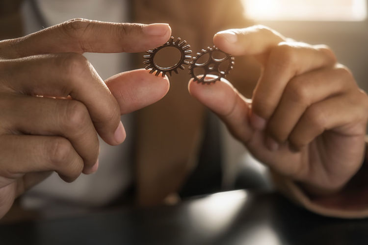 Midsection of person holding gears on table