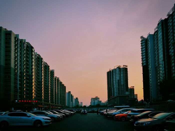 Cars parked on street by buildings against sky during sunset