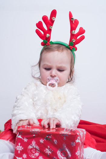 Cute girl with headband sucking pacifier while unwrapping christmas gift against white background