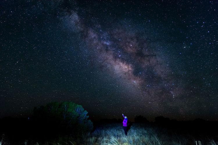 Woman Standing On Field Against Star Field
