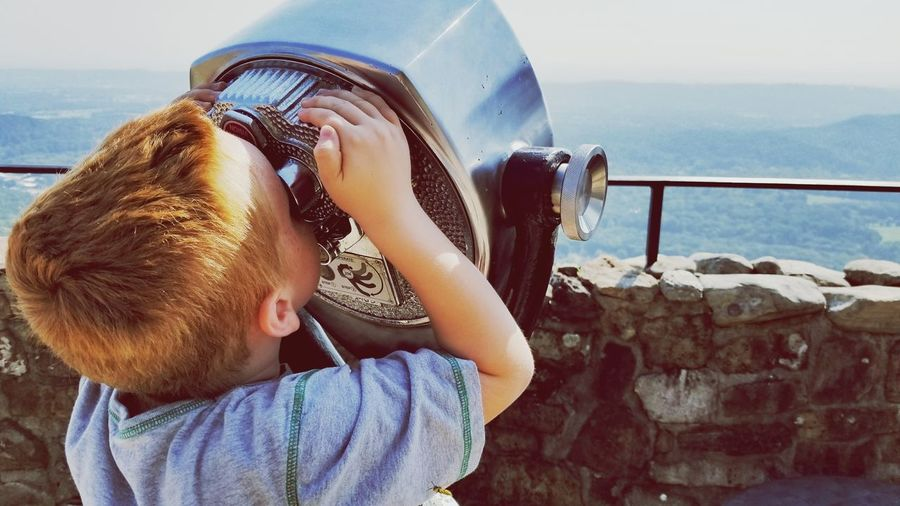 Close-up of boy looking through coin operated binoculars