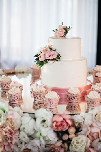 Close-up of flowers by wedding cake on table