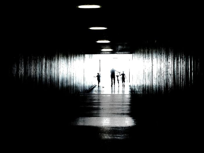 Silhouette of man walking with kids in passage