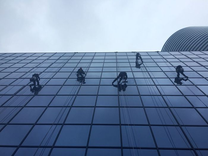 Low angle view of workers cleaning office building against sky