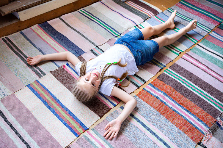 A beautiful cheerful girl with pigtails lies on the floor, on woven rugs. rest after exercise.