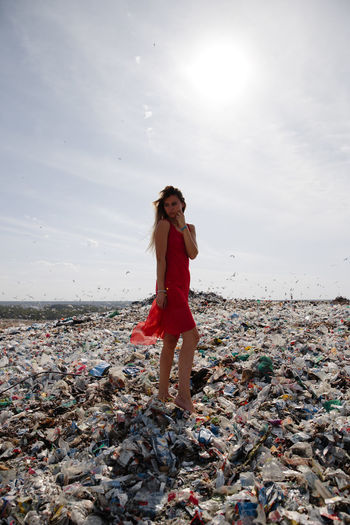 Full length of young woman standing on garbage