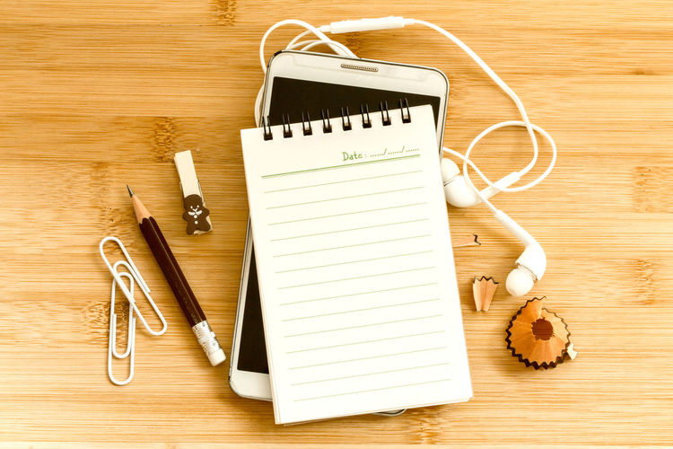 Note pad and pencil with mobile phone on table