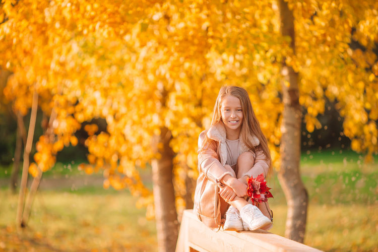Woman wearing red flower plant during autumn