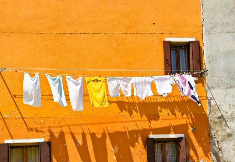 Clothes Drying On Rope Against Orange Building During Sunny Day