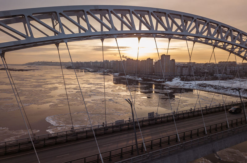 Bridge over river in city during sunset