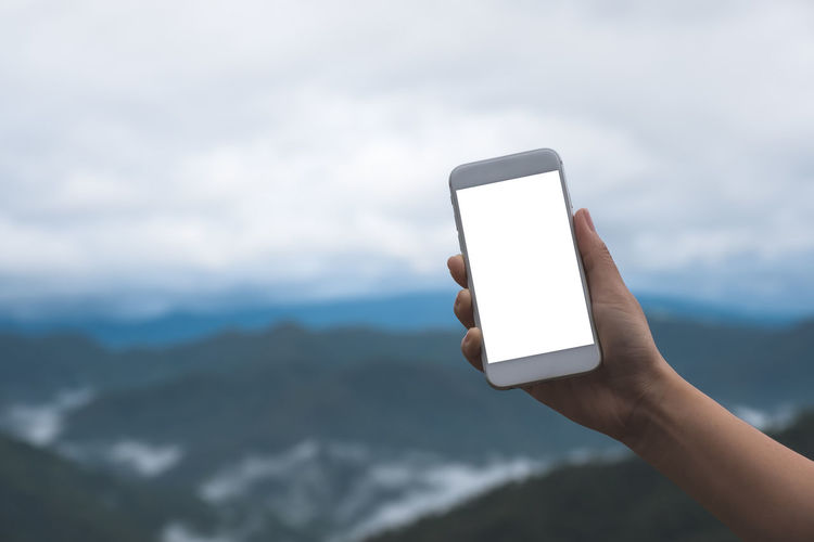 Mockup image of a hand holding and showing white smart phone with blank desktop screen in outdoor with blur green mountains background Smart Screen Phone People Park Outdoor Network Nature Natural Mountain Mockup Mock Mobile Looking Internet Holding Hill Hand Green Forest Fog Empty Display Digital Device Desktop Copy Communication Closeup Close Cellular Cellphone Cell Business Blur Blank Beautiful Background Adult