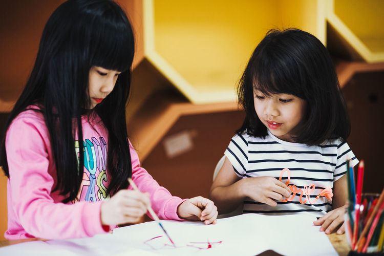 Close-up of girl holding hands on table