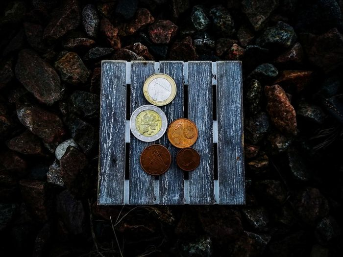 High angle view of coins on wooden plank over stones