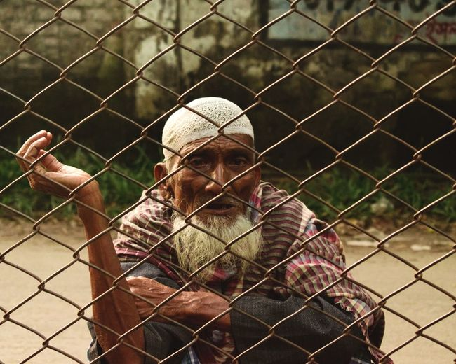 Physically weak but mentally always strong Lifestyles Life Oldman Oldie  Oldschool People Peoplephotography People Watching This Is Strength Standing Young Men Knit Hat Front View Chainlink Fence Casual Clothing Cage Captivity Trapped Confined Space