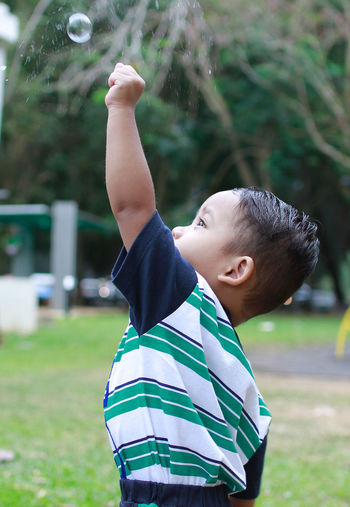 Close-up of boy playing with bubbles in park