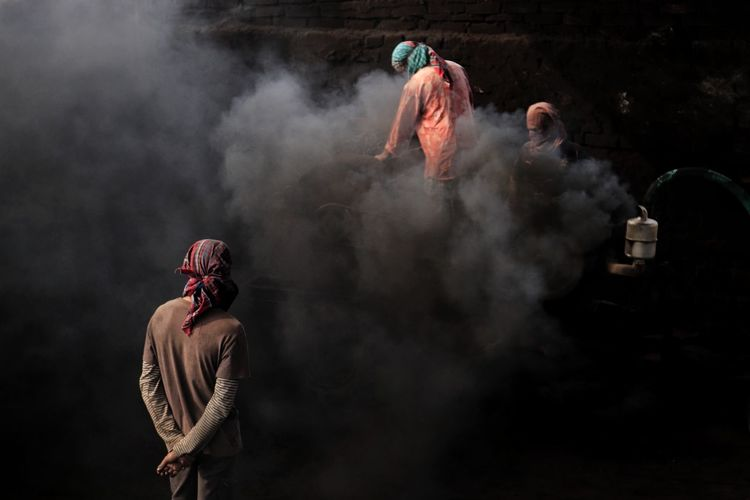 Rear view of people working at brick field in a over polluted environment