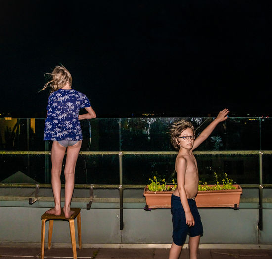 Full length of woman standing by swimming pool at night