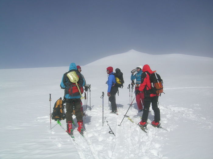 People standing on snowcapped mountain against clear sky