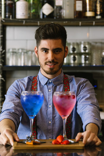 Portrait Of Bartender With Drinks In Bar