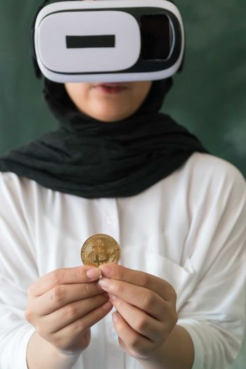 Woman wearing virtual reality simulator while holding bitcoin at home