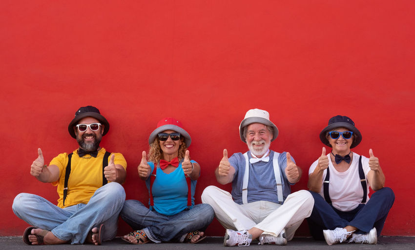Portrait of happy friends showing thumbs up while sitting against red wall