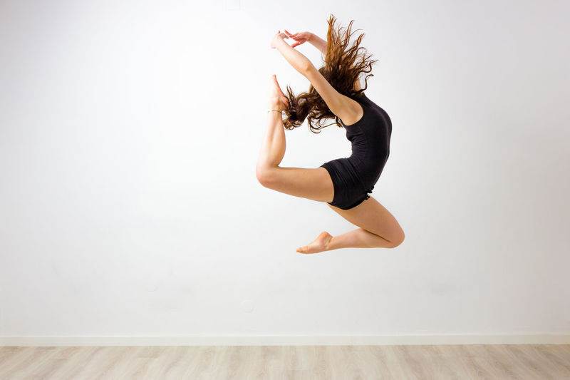 Woman Dancing Against White Wall