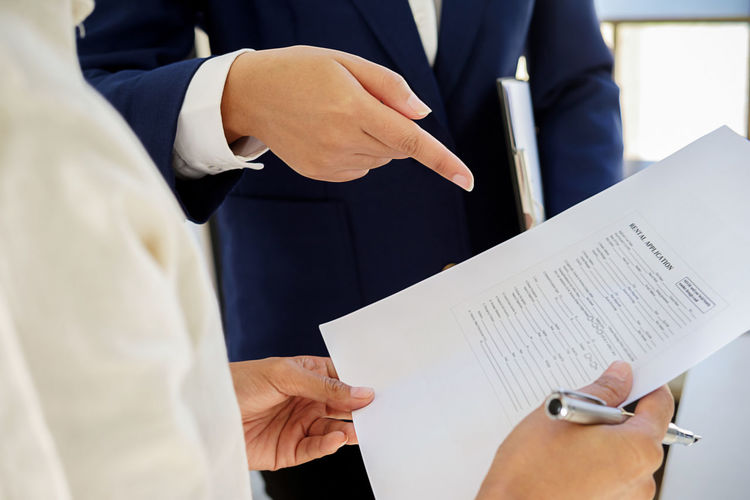 Midsection of salesman explaining document to client
