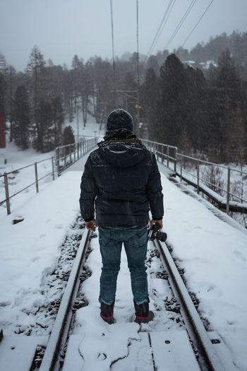 Photographer standing on train track Railway Winter Cold Temperature Snow Rear View Tree Clothing One Person Real People Leisure Activity Full Length Lifestyles Warm Clothing Nature Day Plant Covering Land Transportation Outdoors Extreme Weather
