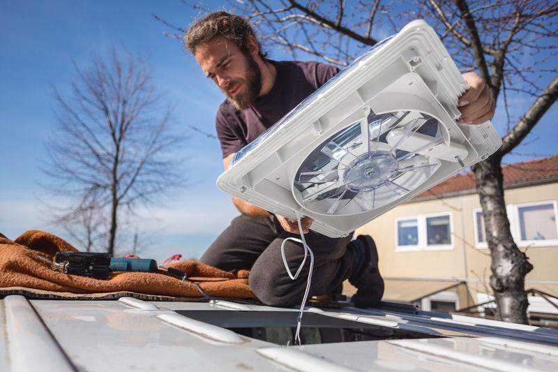 Man holding electric fan on car