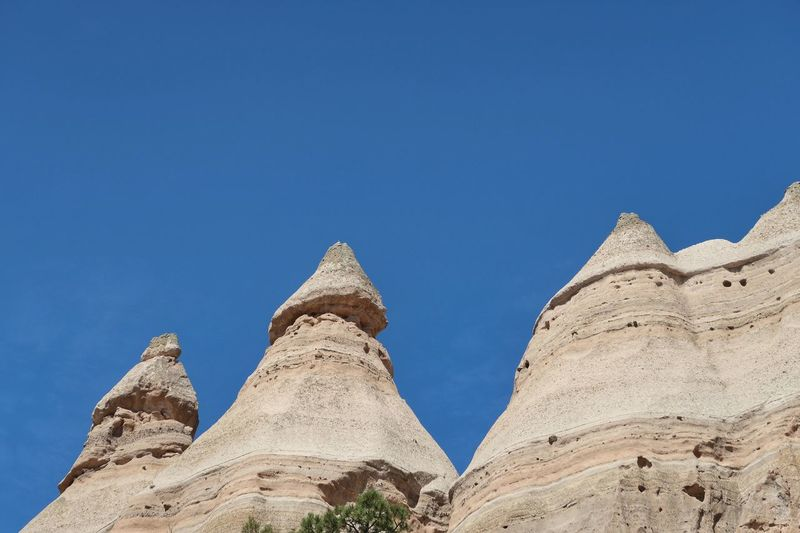 Low angle landscape of triangular rock formations in Kasha-Katuwe Tent Rocks National Monument Kasha-Katuwe Tent Rocks National Monument Kasha-Katuwe New Mexico Rock Formations Tent Rocks EyeEm Selects Sky Blue Clear Sky Nature Low Angle View Day No People Sunlight History The Past Travel Destinations Copy Space Outdoors Travel Ancient Tourism Land