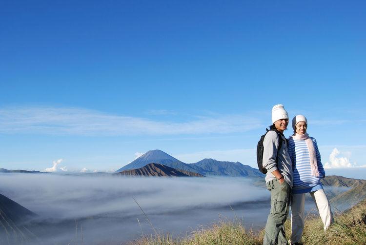 Couple on mountain against blue sky