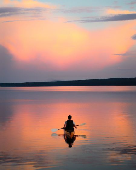 Man Rowing Boat On Lake Against Sky During Sunset