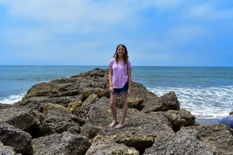 Woman Standing On Rocky Shore Against Sky
