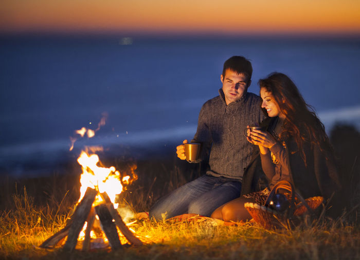 Man and woman sitting on bonfire by land against sky