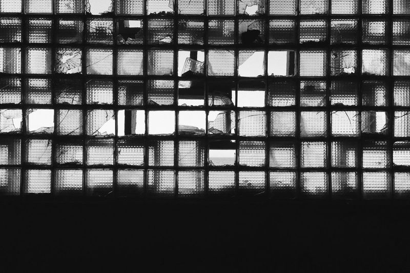 Full frame shot of window with silhouette building in background