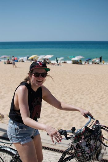 Woman with bicycle at beach against sky