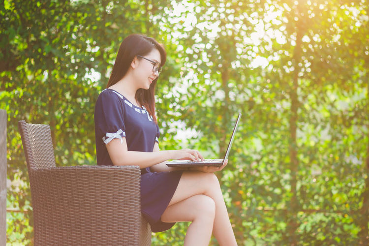 Side view of woman using laptop while sitting on chair