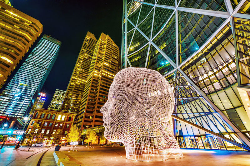 "Night view of the popular ""Wonderland"" sculpture by famous artist Jaume Plensa sits in-front of The Bow tower in Calgary, Alberta,Canada HEAD Alberta ArtWork Architecture Building Exterior Built Structure Calgary Canada City Cityscape Face Famous Place Futuristic Illuminated Modern Night Night View Of City No People Outdoors Sculpture In The City Sky Skyscraper Travel Destinations Wonderland"