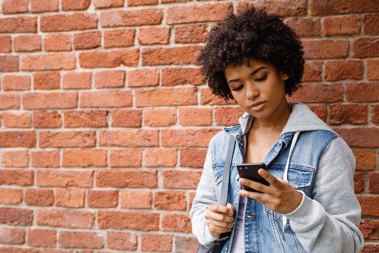 Young woman using mobile phone against brick wall