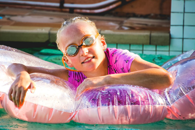 portrait of a young girl relaxing in the pool on pink inflatable One Person Leisure Activity Smiling Happiness Swimming Pool Front View Lifestyles Pool Real People Water Headshot Portrait Swimwear Day Inflatable  Outdoors Eyewear Swimming Goggles Girls Childhood Innocence Inflatable  Pink Color
