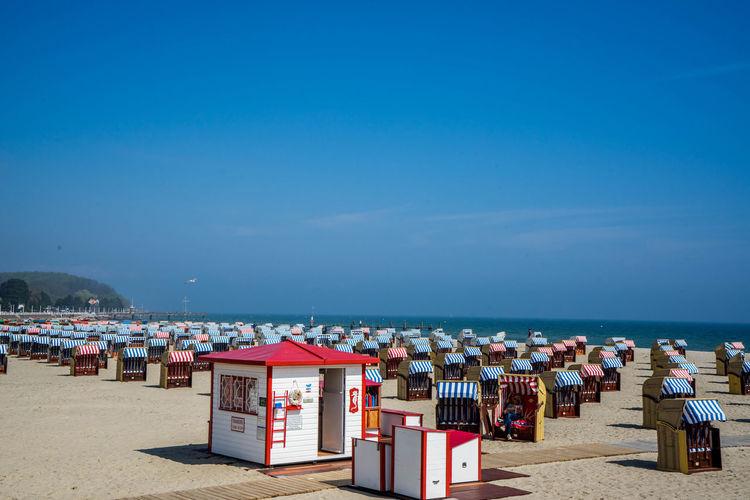 Hooded beach chairs on beach against clear sky