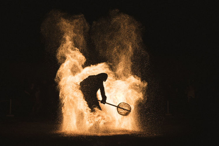 Silhouette Man Performing Stunt In Fire At Night