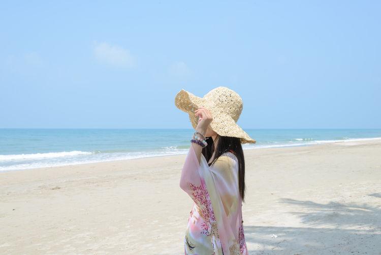 Woman wearing hat on beach against sky