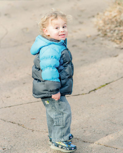 Toddler smiling at camera with winter coat on Babyhood Blond Hair Casual Clothing Childhood Cute Day Focus On Foreground Full Length Happiness Leisure Activity Lifestyles Looking At Camera One Person Outdoors Portrait Real People Smiling Standing Toddler