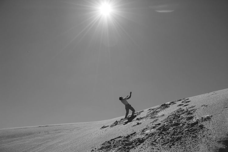 Low Angle View Of Man Climbing On Sand Dune During Sunny Day