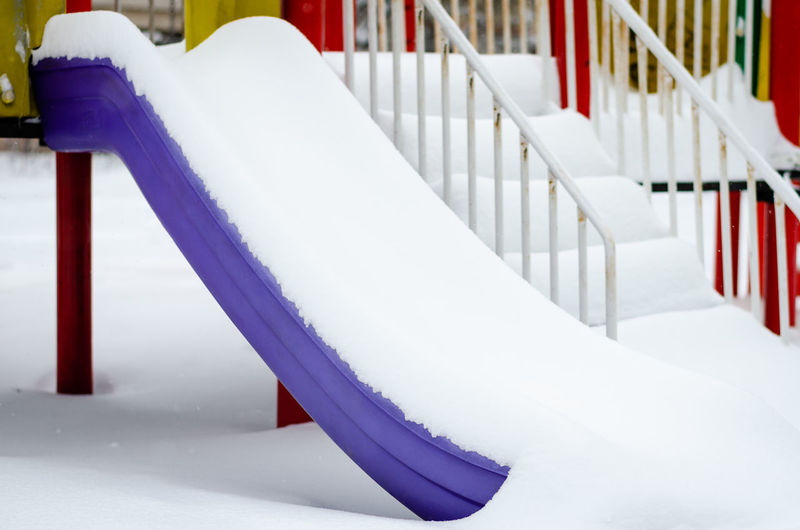 A slide in the park covered with snow in winter White Color No People Railing Focus On Foreground Staircase Close-up Absence Snow Cold Temperature Winter Metal Steps And Staircases White Built Structure Day Purple Playground Snowlandscape Frozen Cold Park Play Empty Fun Child Playground