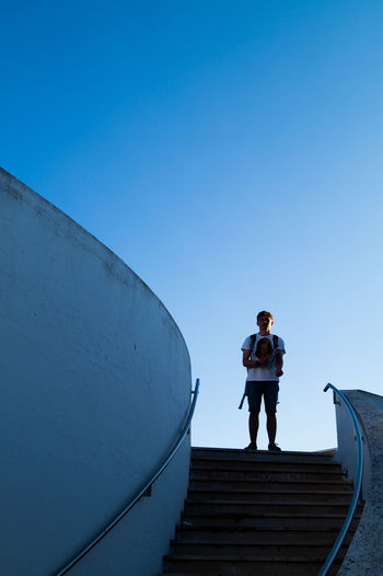 Low angle view of man standing on staircase against clear blue sky