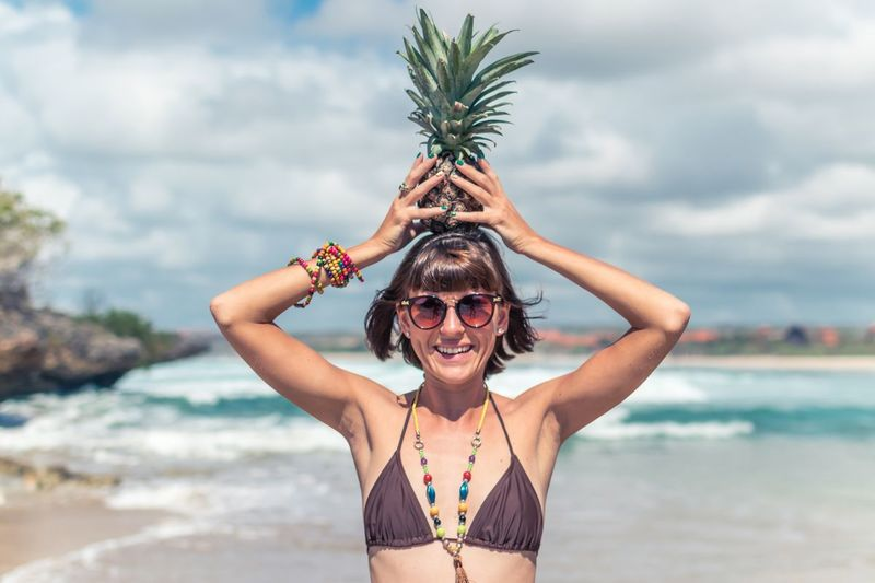 Portrait Of Seductive Women Holding Pineapple At Beach Against Sky