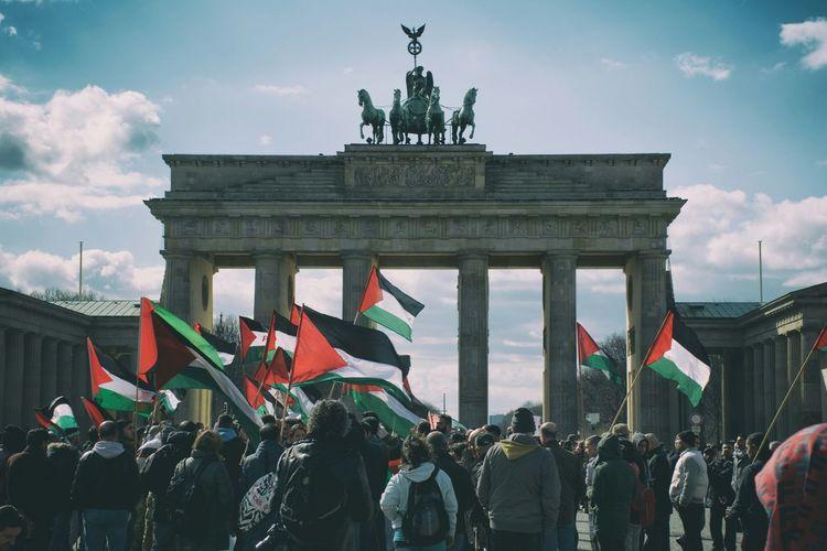 Crowd Waving Palestinian Flags At Brandenburg Gate Against Sky